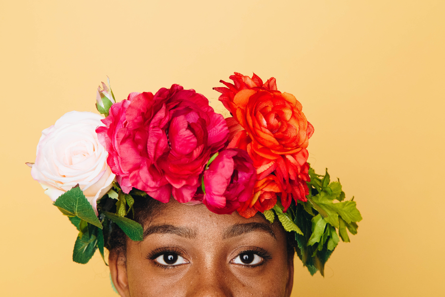 Black woman with flower grown on in front of a yellow background