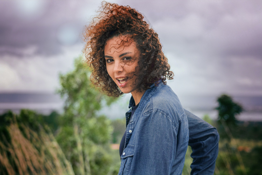 Black girl staring at camera with mouth open while curly hair blows in the wind