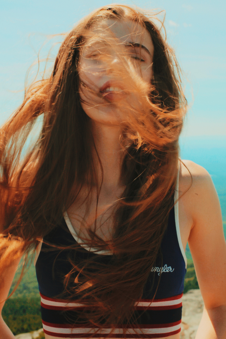 Girl with red frizzy hair flowing in the wind at the beach
