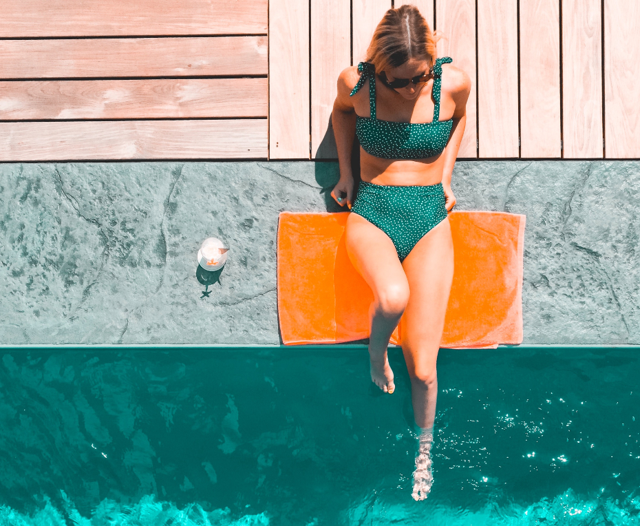 girl with blonde highlights hangs on by the pool in her bikini swimsuit