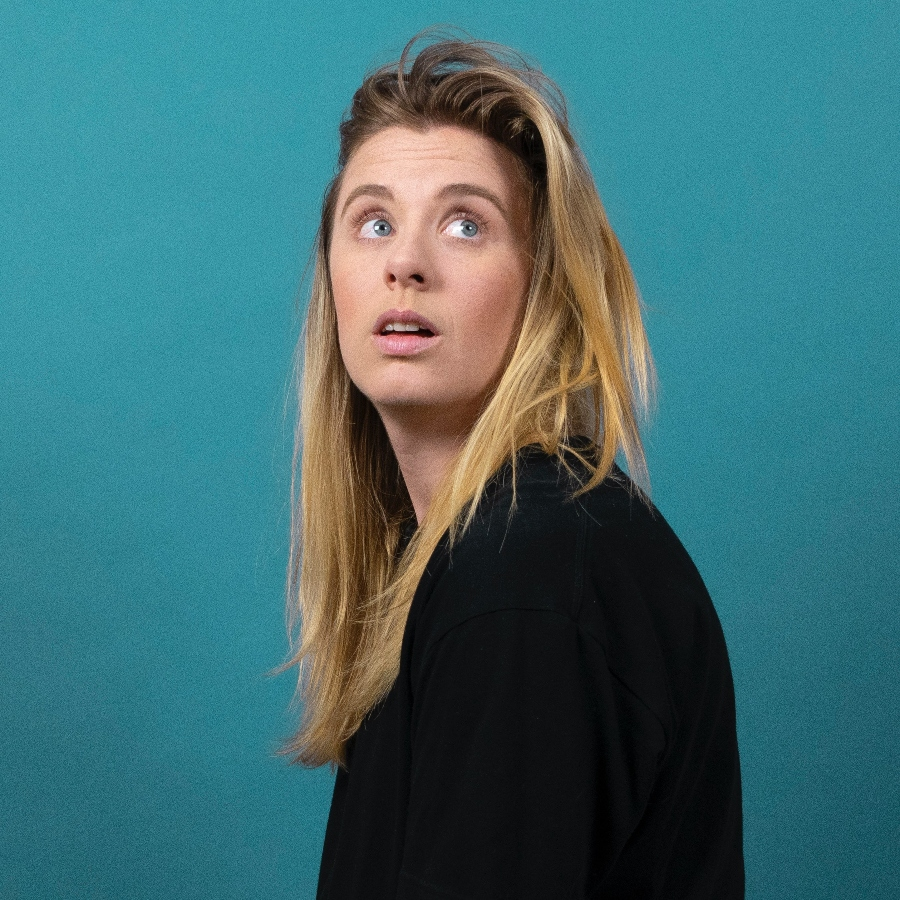 Girl with 1B hair posing in front of turquoise background while looking at something off to the side and above the camera